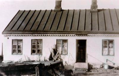 """Torpet från baksidan med Anna Lindros på 1920-talet. Längst ner till höger, syns  """"avloppet"""" som rinner ut i en hink. Fotograf okänd."""