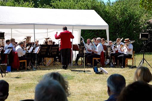 Andreas Wetterlund dirigerar dagens Limhamns Brassband i Soldattorpets trädgård.
