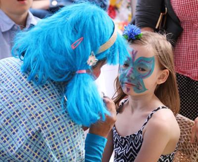 Annette Lindén, ansiktsmålaren, som dagen till ära var lika färgglad i håret som barnen i ansiktet.