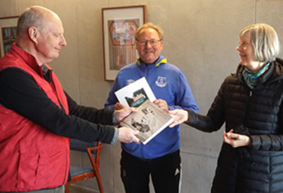 Museiföreningens Rolf Hansson överräcker boken med Limhamnsfoton till Barbro Borglundh. I mitten syns en annan av de lyckliga vinnarna Peter Anderberg.